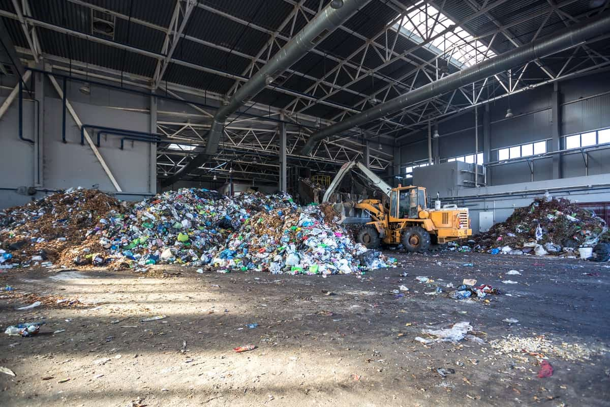 An excavator sifts and sorts through waste material on an MRF dumping floor