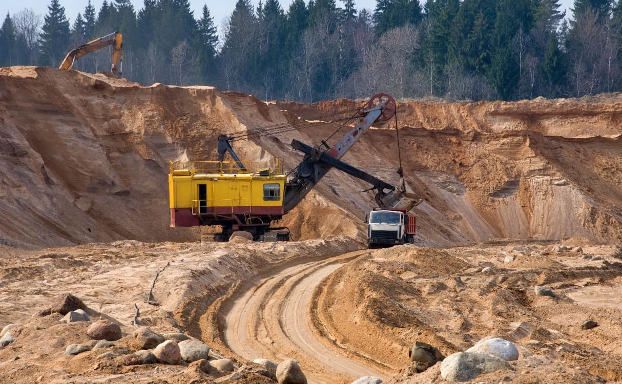Heavy equipment loads sand into a dump truck to be carried to a classification plant