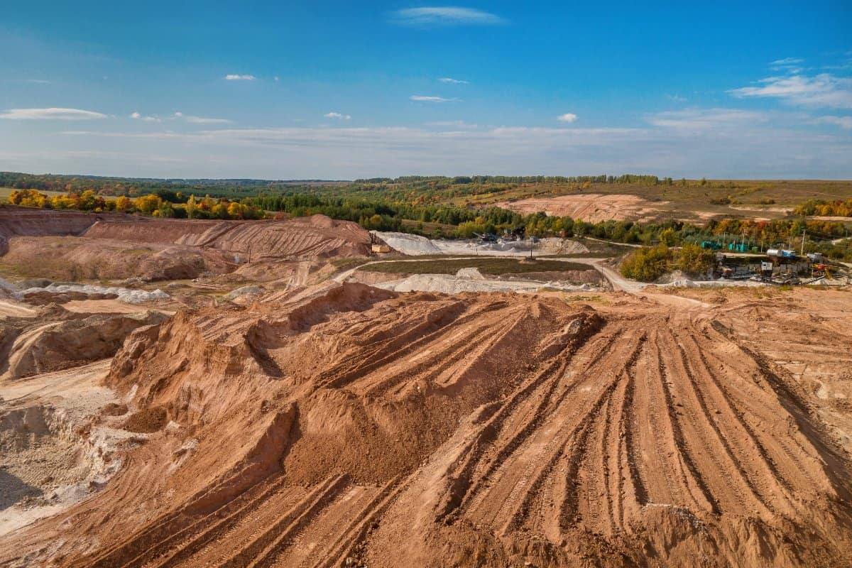 A panoramic view of a quarry where excavation of construction aggregates like sand, gravel, and clay are mined. Excavation equipment is visible in the background alongside aggregate processing and screening equipment.